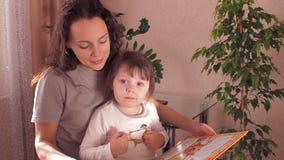 Mamma som läser en bok till barn arkivfilmer