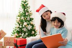 Mamma som läser en bok till hennes gulliga dotter royaltyfria bilder