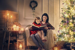 Mamma som läser en bok till hennes gulliga dotter royaltyfri bild