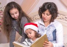 Mamma som läser en julberättelse med barn Arkivbild
