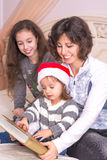 Mamma som läser en julberättelse med barn Fotografering för Bildbyråer