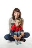 Mamma som rymmer hennes son i armar Fotografering för Bildbyråer