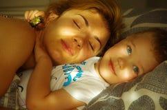 Mamma som sover med sonen Fotografering för Bildbyråer