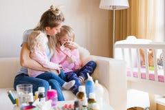 Mamma som tar omsorg av hennes sjuka barn arkivfoton