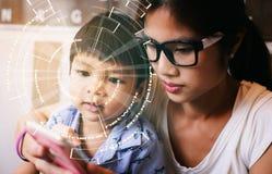 Mamma som undervisar ungen för hög tech att använda teknologiapparaten Arkivfoton