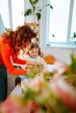 Mamma som visar hennes lilla dotter hur man tar omsorg av växter royaltyfri foto