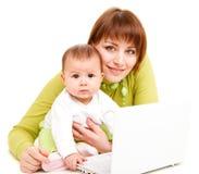 Mamma und Schätzchen, die am netbook arbeiten Lizenzfreie Stockbilder