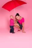 Mamma und Sohn unter einem roten Regenschirm Lizenzfreie Stockbilder