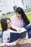 Mamma und Tochter, die ein Buch lesen Stockfotografie