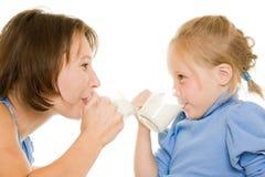 Mamma und Tochter trinken Milch. stockfoto