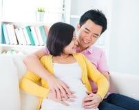 Mamma und Vati mit den Händen auf dem Baby Lizenzfreie Stockfotos
