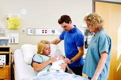 Mamma voedende baby met Papa en verpleegster die kijken stock fotografie