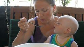Mamma voedende baby mooie soep in de koffie Het jonge geitje die de lepel likken wil nog eten Blondejongen in een groene t-shirt stock footage