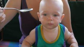 Mamma voedende baby mooie soep in de koffie Het jonge geitje die de lepel likken wil nog eten Blondejongen in een groene t-shirt stock videobeelden