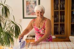 Mamma zu Hause, die mit einem Dampfeisen - Hauswirtschaftsleiterin bügelt Lizenzfreie Stockbilder