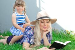 Mammablondinen i en hatt och hennes dotter ligger på gräset och läser en bok, lycklig familj royaltyfria bilder