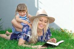Mammablondinen i en hatt och hennes dotter ligger på gräset och läser en bok, lycklig familj arkivbild