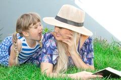 Mammablondinen i en hatt och hennes dotter ligger på gräset och läser en bok, lycklig familj royaltyfria foton