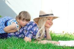 Mammablondinen i en hatt och hennes dotter ligger på gräset och läser en bok, lycklig familj arkivfoto