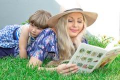 Mammablondinen i en hatt och hennes dotter ligger på gräset och läser en bok, lycklig familj arkivfoton
