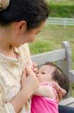 Mammaborst die - haar babymeisje voeden Stock Foto's