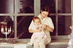 Mammabrunettsammanträde på fönster och kramar det lilla gulliga litet paraplyGet Royaltyfria Bilder