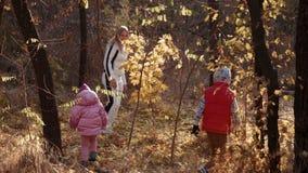 Mammagangen met de dochter en de zoon in de herfstpark stock videobeelden