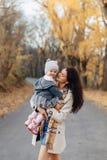 Mammalek för den unga kvinnan med den lilla dottern på hösten parkerar vägen fotografering för bildbyråer