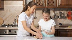 Mamman är undervisa hennes tonåriga dotter hur man lagar mat deg i köket hemma lager videofilmer