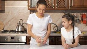 Mamman är undervisa hennes tonåriga dotter hur man lagar mat deg i köket hemma stock video