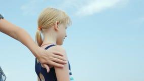 Mamman applicerar hennes sunscreen för dotter` s Skydd från solen på semester lager videofilmer