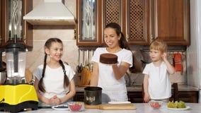 Mamman bakar en kaka med hennes två lilla döttrar i köket stock video