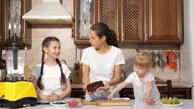 Mamman bakar en kaka med hennes två lilla döttrar i köket arkivfilmer