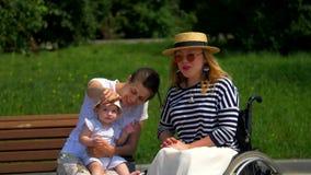 Mamman, barnet och flickan i en rullstol, sitter sidan - förbi - sidan och ler arkivfilmer