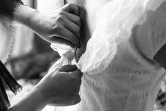 Mamman drar igen blixtlåset på brudens bröllopsklänning arkivfoto