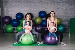 Mamman för två behandla som ett barn den unga sportar och flickor gör övningar tillsammans i royaltyfri foto