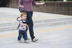 Mamman försäkrar hennes barn under en gå Arkivfoton