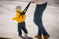Mamman försäkrar hennes barn under en gå Arkivbild
