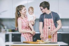 Mamman farsa och behandla som ett barn lite matlagningkakor i köket tillsammans a arkivbilder