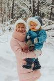 Mamman går med barnet i vintern i natur Familjen går i natur i vinter Vinterskogsnö parkerar royaltyfri fotografi