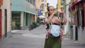 Mamman går på gatan med hennes behandla som ett barn i en rem, medan resa till Spanien och tar bilder av sikten på hennes mobil stock video