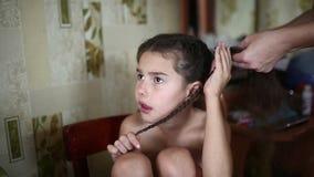 Mamman gör dottern kvinnligt flickahår att fläta sammanträde lager videofilmer