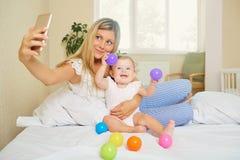 Mamman gör ett foto på telefonen med behandla som ett barn i rummet Salfie Royaltyfri Fotografi