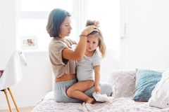 Mamman gör råttsvansar till hennes liten flicka Royaltyfri Fotografi