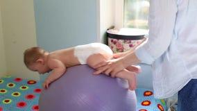 Mamman g?r ?vningar f?r utveckling med behandla som ett barn p? fitballen Behandla som ett barn utvecklingsbegreppet och att att  stock video