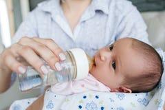 Mamman ger det nyfött behandla som ett barn vatten från en flaska Royaltyfri Bild