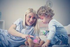 Mamman har lek med hennes behandla som ett barn pojken i vardagsrum Royaltyfria Foton