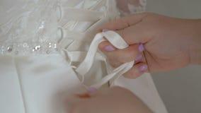 Mamman hjälper bruden att bära en bröllopsklänning stock video