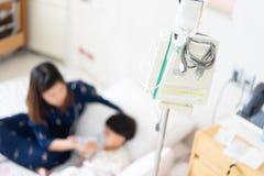 Mamman hjälper den sjuka sonen i sjukhuset royaltyfri bild