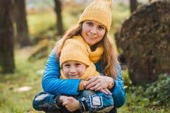 Mamman i en gul hatt kramar hennes son i en gul hatt royaltyfria bilder